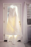 Wedding Dress. A brides wedding dress hangs in front of a door hours before the ceremony Royalty Free Stock Photos