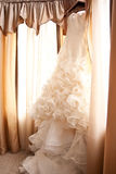 Wedding Dress. Brides wedding dress hanging by a window Stock Image