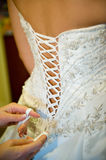 Wedding dress. The bridesmaid helps the bride to lace up a corset Stock Images