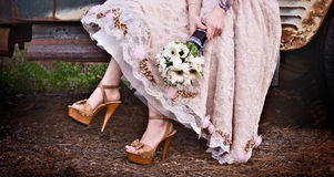 Wedding Dress and bouquet. Brides wedding dress and shoes holding a bouquet Royalty Free Stock Photography