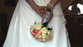Wedding dress and bouquet. A bride holds a bouquet of flowers behind her back as she prepares for her wedding stock video footage