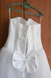 Wedding dress with a bow. Wedding dress of the bride with a bow on a hanger Royalty Free Stock Photos