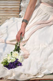 Wedding dress bride and bouquet. Body and hand of a bride in wedding dress and a bouquet, shown as happy in marriage Royalty Free Stock Photos