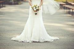 Wedding dress. Bride holding a bouquet Stock Photos