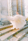 The wedding dress of the bride is overblown by the wind. The bride is standing on the antique staird of the old gothic stock image