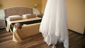 Wedding Dress Bride preparing for the ceremony, the bride's bouquet lies on a bed.  stock video