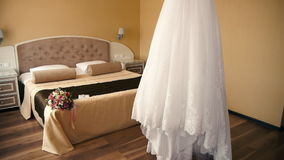 Wedding Dress Bride preparing for the ceremony, the bride's bouquet lies on a bed.  stock video footage