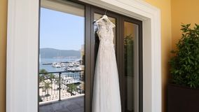 Wedding Dress The bride`s dress hangs on the window, in which th stock footage