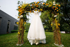 Wedding dress. The bride's wedding flowers facing the sun hanging in the door Royalty Free Stock Images