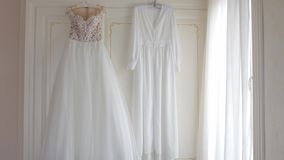 Wedding dress and cape hanging on hangers in the apartment stock video