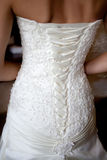 Wedding dress close-up. Closeup photo of beautiful bride's back in wedding dress Royalty Free Stock Image