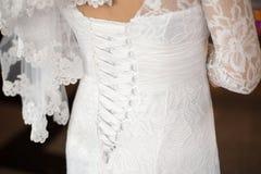 Wedding dress close-up. Close up photo of beautiful bride's back in wedding dress Royalty Free Stock Photo