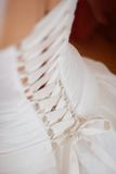 Wedding dress corset. Detail of a woman's wedding dress gown showing curve of back with corset style tie back and veil stock photo