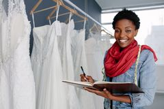 Wedding dress designer working in her boutique. Portrait of smiling female bridal store owner with a diary. Wedding dress designer working in her boutique Royalty Free Stock Photo