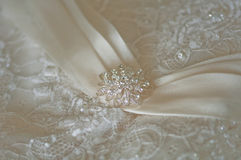 Wedding dress detail. Detail of lace wedding dress with ribbon and crystal broach Royalty Free Stock Images