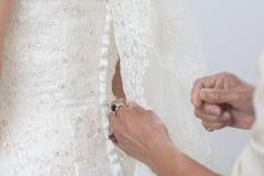 Wedding dress detail. Woman helping the bride Royalty Free Stock Photos
