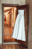 Wedding dress on a door in a hotel room. White wedding dress on a door in a hotel room Stock Photography