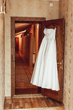 Wedding dress on a door in a hotel room. White wedding dress on a door in a hotel room Royalty Free Stock Photography
