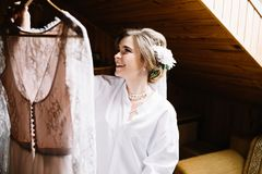 Wedding dress embroidered with crystals and pearls hangs over th. Attractive young bride is smiling while choosing wedding dress Stock Photography