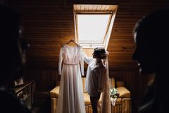 Wedding dress embroidered with crystals and pearls hangs over th. Attractive young bride is smiling holding wedding dress Stock Image