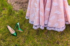 Wedding dress. Wedding emerald bridesmaid shoes on the green grass on the background of the dress Royalty Free Stock Photo