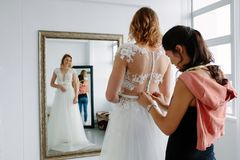 Wedding dress fitting in bridal boutique. Woman assistant helping female in trying wedding dress in a shop. Bridal shop owner assisting young bride getting Stock Image
