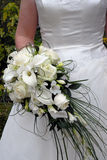 Wedding dress and flowers. White bridal dress seen from the front, with white flowers in the bouquet Royalty Free Stock Photography