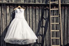 Wedding dress. In front of an old wooden wall
