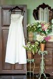 Wedding dress on a hanger. The wedding dress on a hanger hangs on a door near an ancient dresser and flowers Stock Photos