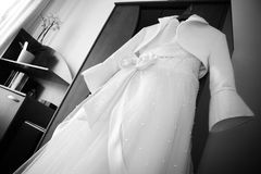 Wedding dress hanging. White bridal dress decorated with pearls and bow hanging in the room Stock Photos