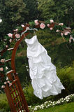 Wedding dress hanging from an arbor. Decorated with roses Stock Images