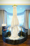 Wedding  dress hanging on ceiling in luxury room. Royalty Free Stock Image