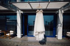 Wedding dress hanging on a hanger near the hotel Stock Image