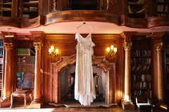 Wedding dress hanging in a library.  Stock Photos