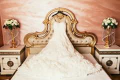Wedding dress hanging on luxury bed decorated with flowers Royalty Free Stock Photography