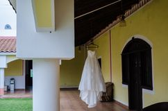 Wedding dress hanging over the corridor of a hotel interior, wooden bars on the roof of a hotel corridor royalty free stock image