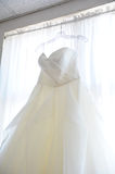 Wedding Dress Hanging Up in Window Royalty Free Stock Photography