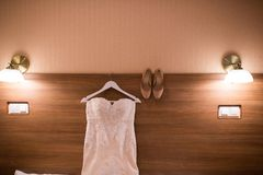 Wedding dress hanging on the wall in the room and bridal beige shoes. Image of the bodice of a beige wedding dress on a wooden whi. Te hanger. Wedding gown Royalty Free Stock Photos
