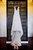 Wedding dress hanging on the wall with shoes on the floor, tungsten light in background royalty free stock images