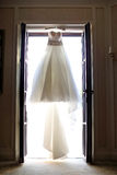 Wedding dress. Hanging on the window Royalty Free Stock Image