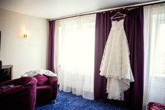 Wedding Dress Hanging in a Window. Beautiful wedding dress hanging on window on a background of purple curtains in hotel room Stock Image