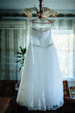 Wedding dress hanging in a window Royalty Free Stock Images