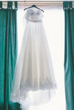 Wedding dress hanging in a window. Green curtains royalty free stock photo