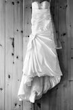 Wedding dress hanging on a wood panel wall. For a country wedding Stock Images