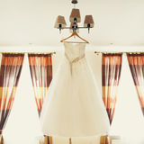 A wedding dress hangs on a chandelier Stock Photos