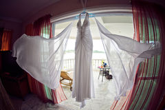 Wedding dress at the hotel on the background of the pool, ocean and mountains Stock Photos