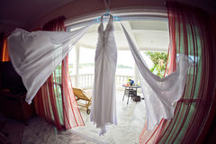 Wedding dress at the hotel on the background of the pool, ocean and mountains Royalty Free Stock Photos