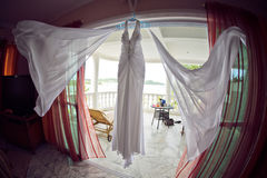 Wedding dress at the hotel on the background of the pool, ocean and mountains Stock Image
