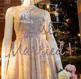 Wedding dress Just Married tag. Just Married tag on show-window of a French fashion boutique with short elegant silk wedding dress Stock Images