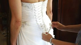 Wedding dress lacing. Lacing up the back of a white wedding dress stock video